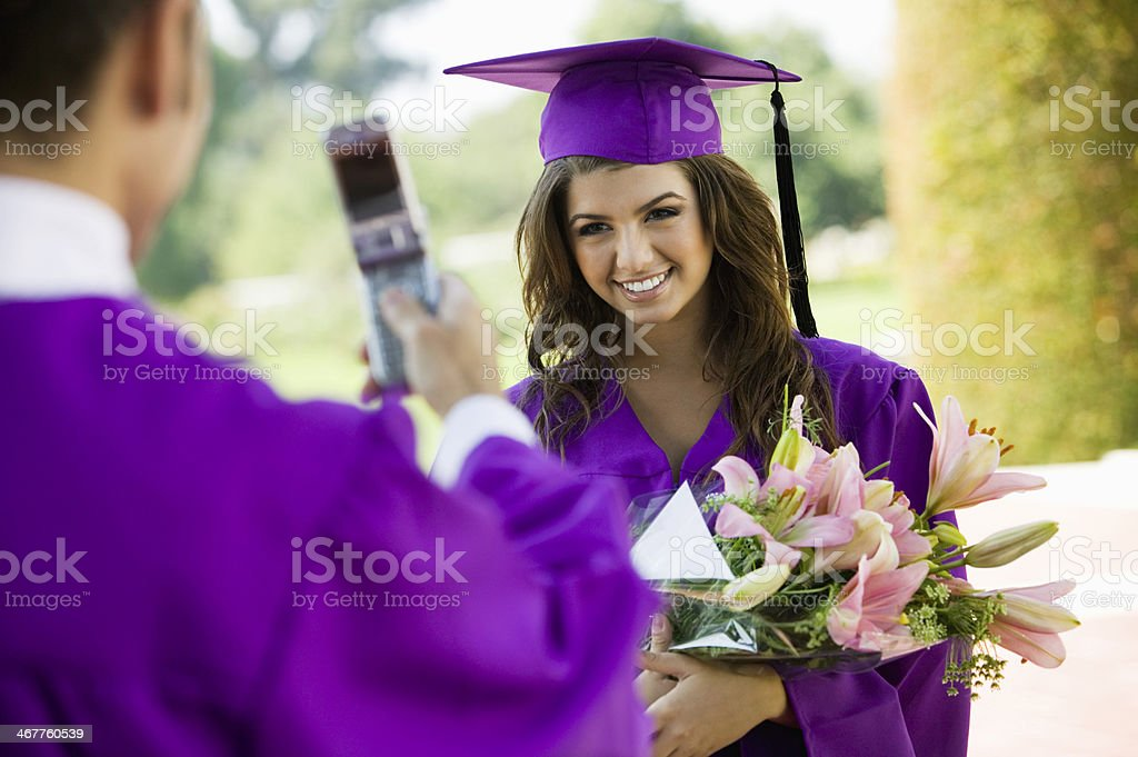Graduate tener fotografía tomada con cámara de teléfono celular - foto de stock