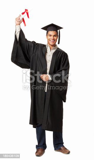 Male graduate holds up a diploma while wearing a graduation gown. Vertical shot. Isolated on white.