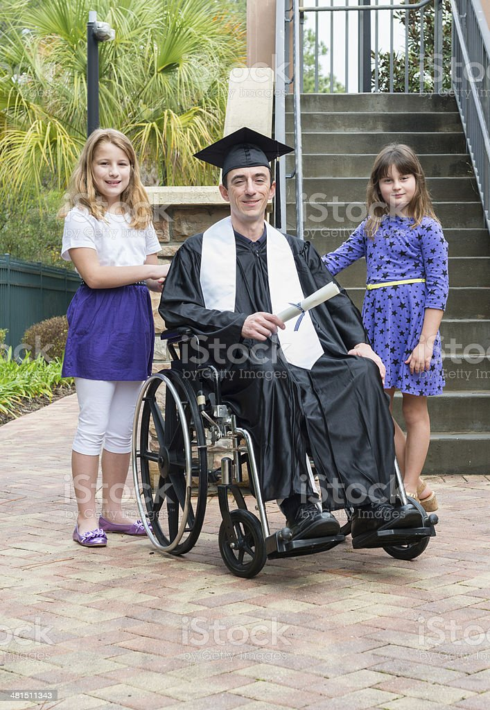 Graduate in wheelchair with daughters stock photo