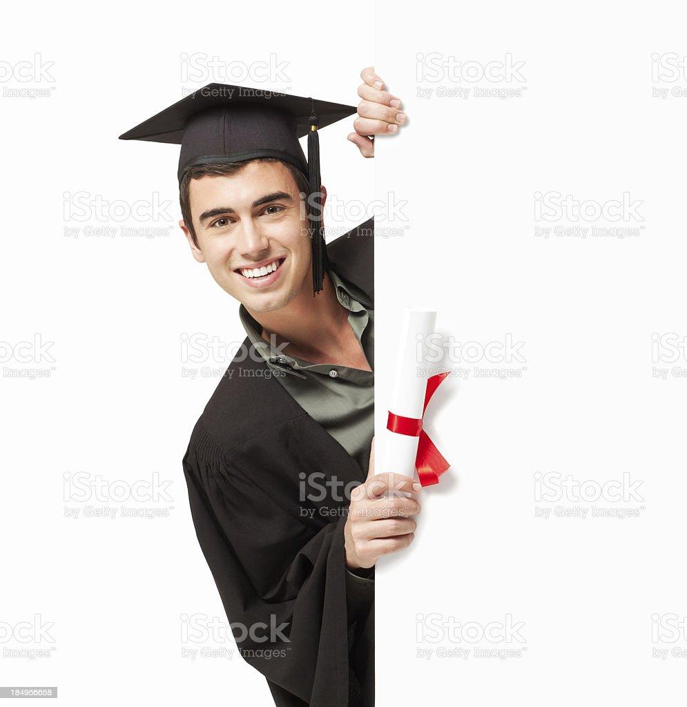 Graduate Looking Around a Corner stock photo