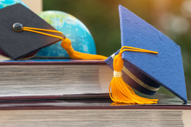 Graduate or Education knowledge learning study abroad concept : Blue Graduation cap on opening textbook with blur of america earth world globe model map in Library room of campus, Back to School stock photo