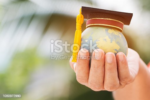 istock Graduate or Education knowledge learning study international abroad concept : Graduation cap on opening textbook with blur earth world globe model map in outdoor of campus, Back to School 1050972990