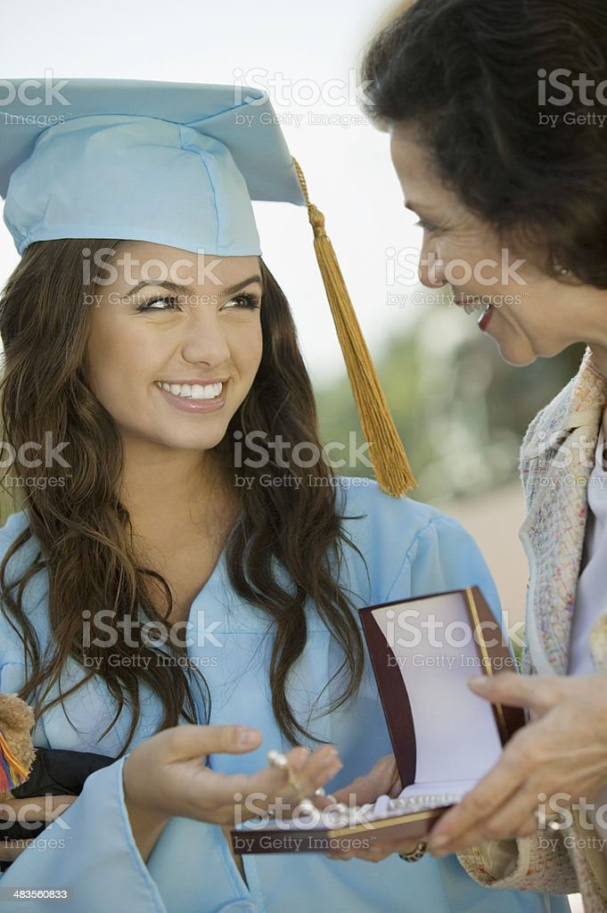Graduate Receiving Gift from Grandmother stock photo