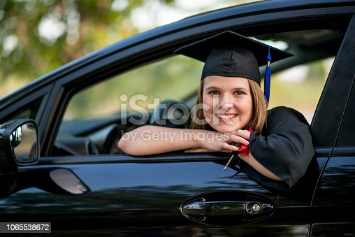 A graduating student in mortar board and academic gown sits behind the wheel of a new car she has been given. She is holding the keys which have a red bow tied around them.