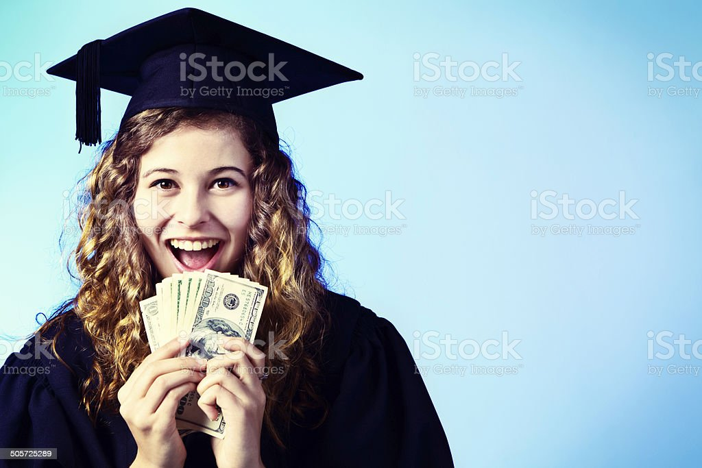 Graduate smiles, holding sheaf of banknotes. Degree equals guaranteed employment This beautiful young honey-blonde woman in academic dress smiles happily as she holds up a sheaf of banknotes. This could be her reward for getting her degree or symbolic of her improved earning power. Copy space on the pale blue background. Achievement Stock Photo
