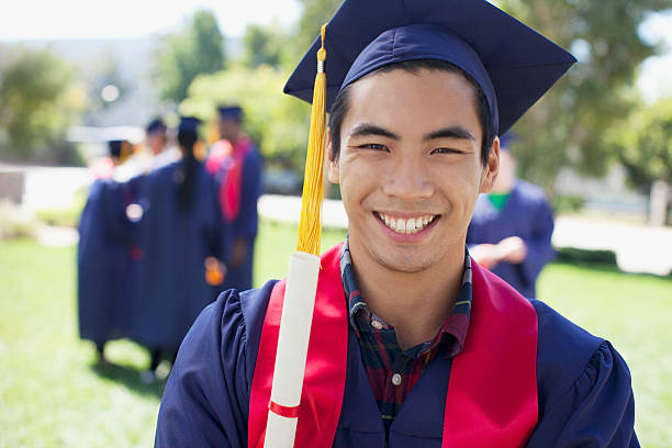 Graduate smiling outdoors stock photo