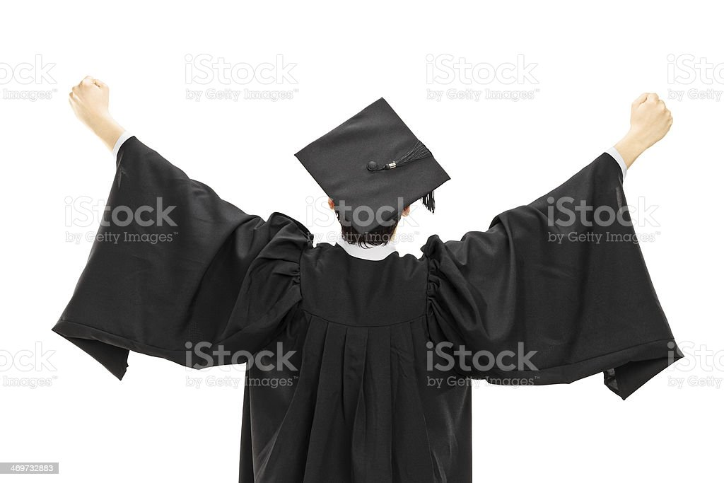 Graduate student in graduation gown with raised hands, rear view stock photo