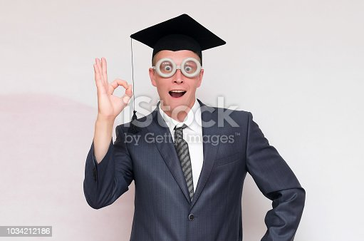 Graduate student is showing Okey gesture sign isolated on gray background. Education concept.
