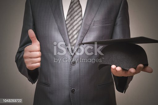 Graduate student holding in hand a graduation cap and is showing a thumbs up isolated on gray background.