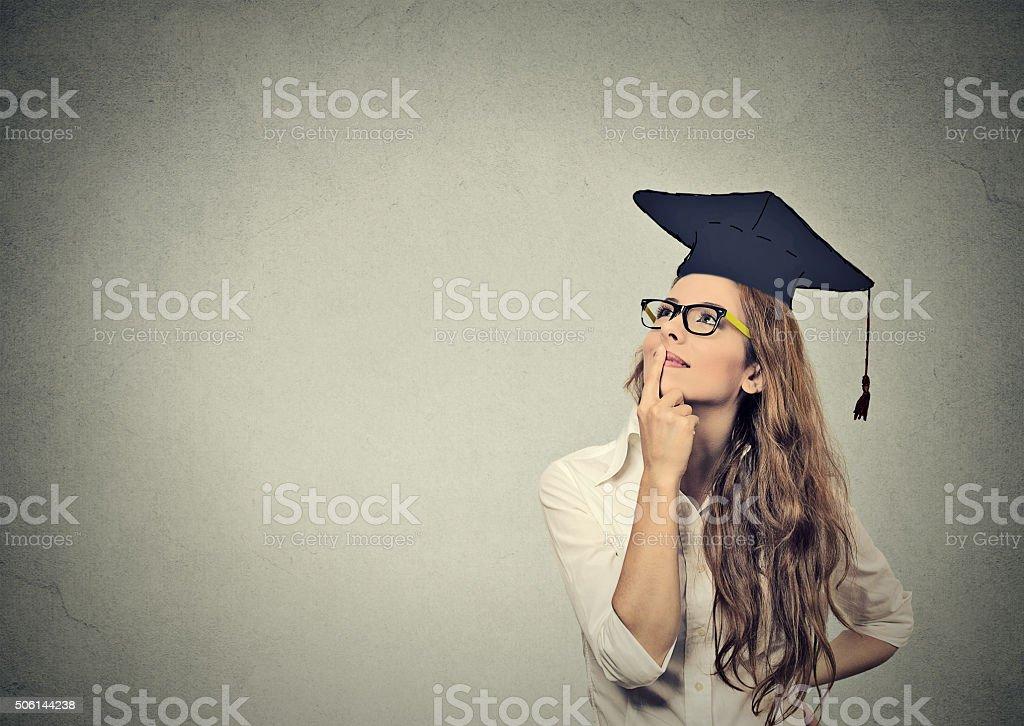 Estudiantes graduados mujer en traje de la tapa mirando hacia arriba de pensamiento foto de stock libre de derechos