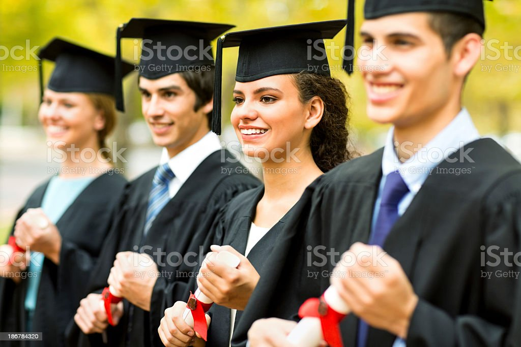 Graduate Students Holding Diplomas While Looking Away On Campus royalty-free stock photo