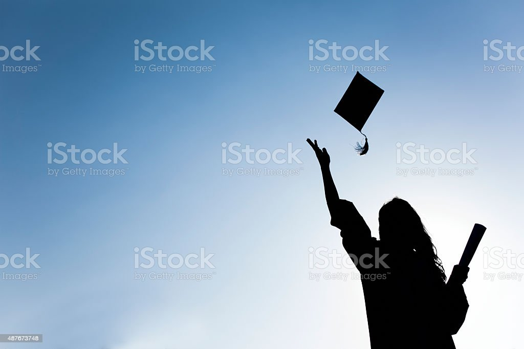 Graduate students tossing up hats over blue sky stock photo