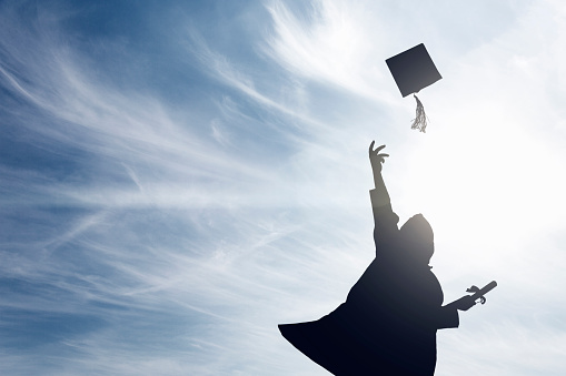 Graduate students tossing up hats over blue sky