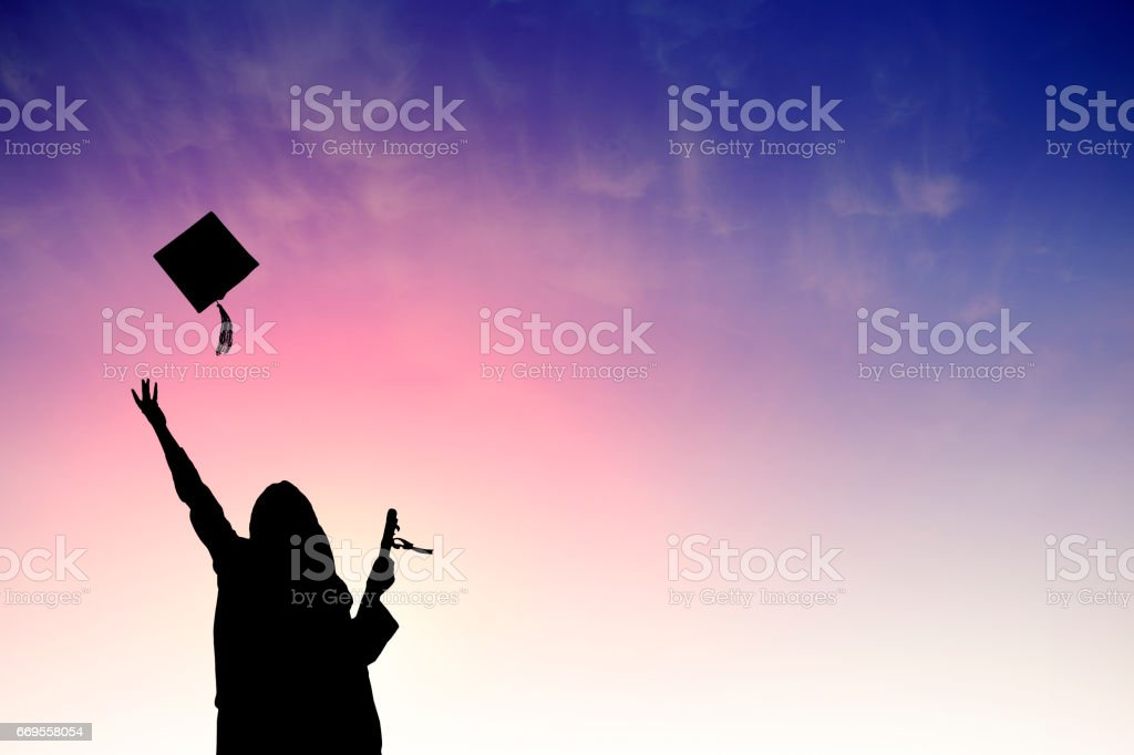 Graduate students tossing up hats over sky stock photo