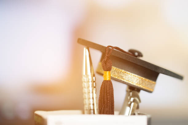 Graduate study abroad international school concept : Black graduation cap on silver pen in bottle. Education is knowledge and power for learning and success in your life, vintage tone stock photo