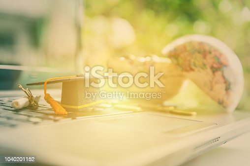 istock Graduate study abroad program and open or expand world view concept : Graduation cap or hat, certificate or diploma and coins in world globe on a laptop, depicts cost or money expense in education. 1040201152