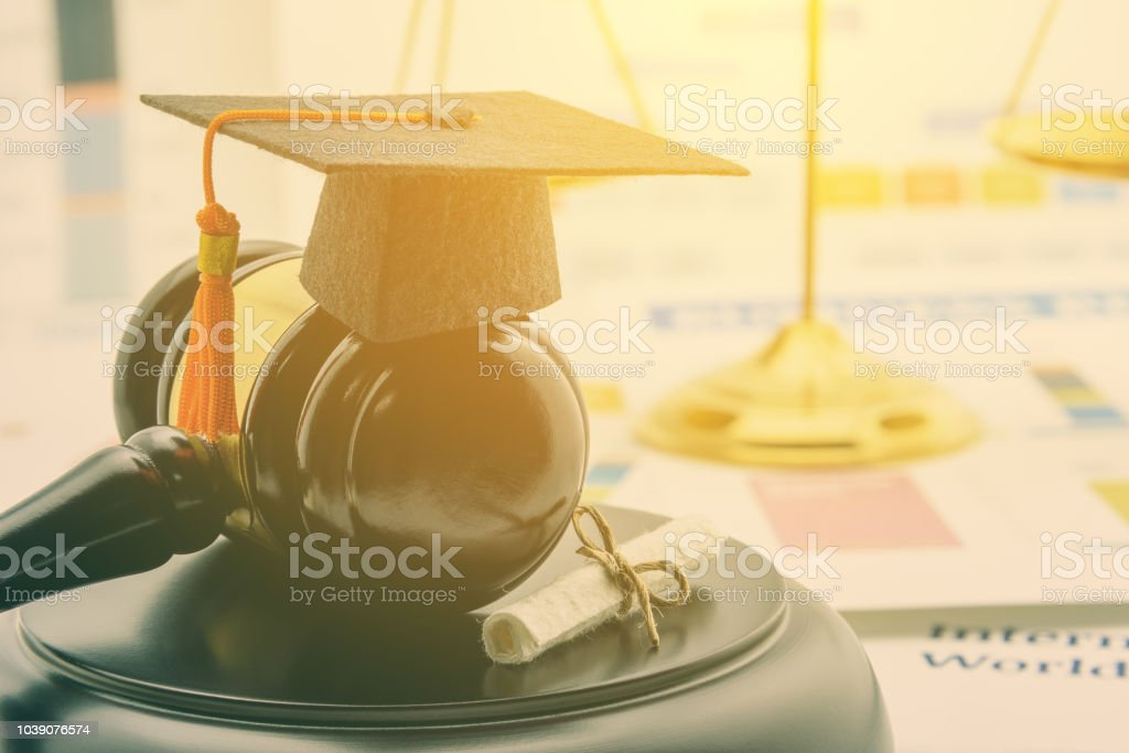 Graduate study abroad program concept : Graduation cap on a gavel, balance scale of justice behind, a certificate. Graduate study abroad program is a program that accept students from foreign country stock photo