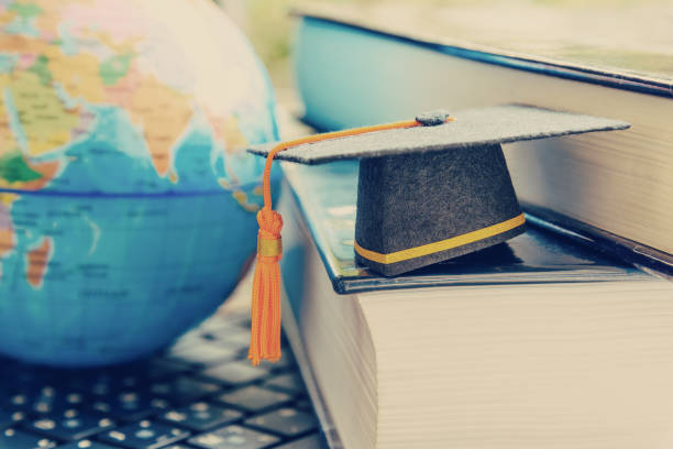 diplom-studienprogramm für öffnung oder weltbild konzept graduation cap oder hut, globus weltkarte und ausländischen buch auf einem laptop, stellt eine errungenschaft oder lange entfernten lernerfolg zu erweitern - militärisches training stock-fotos und bilder