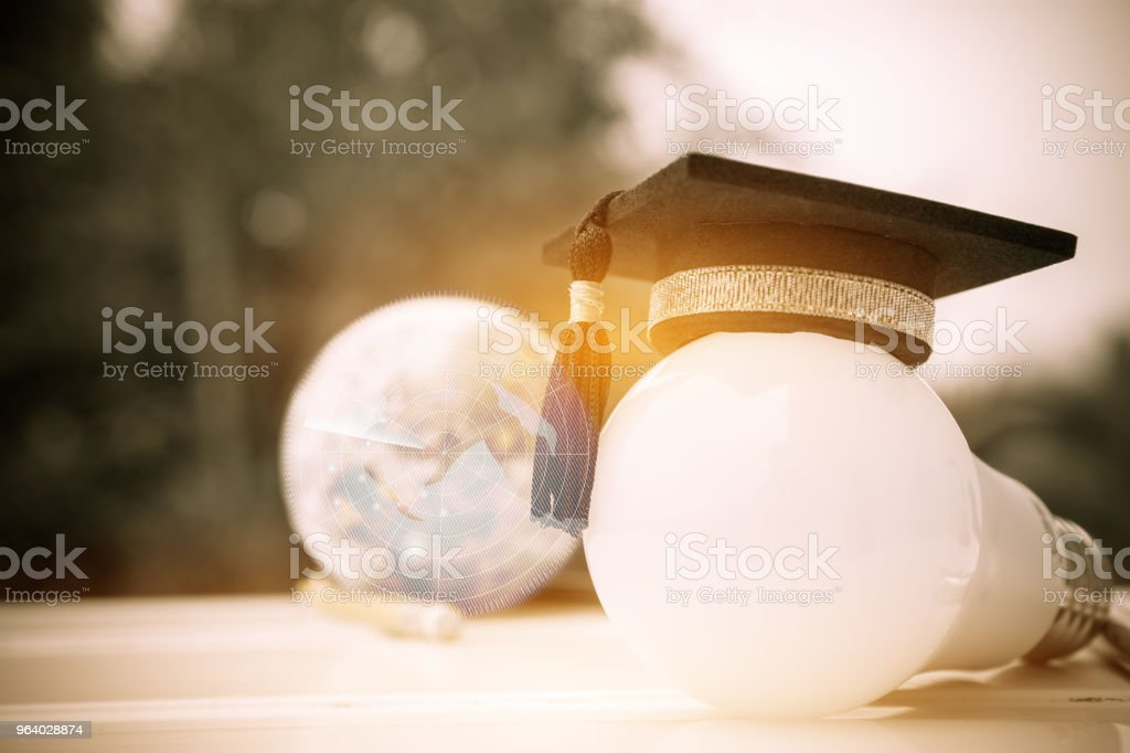 Graduate study, Education knowledge power concept: Hands holding light bulb with Graduated cap. Conceptual for Educational Sparked Navigation for successs study or business world. Back to School ideas - Royalty-free Achievement Stock Photo
