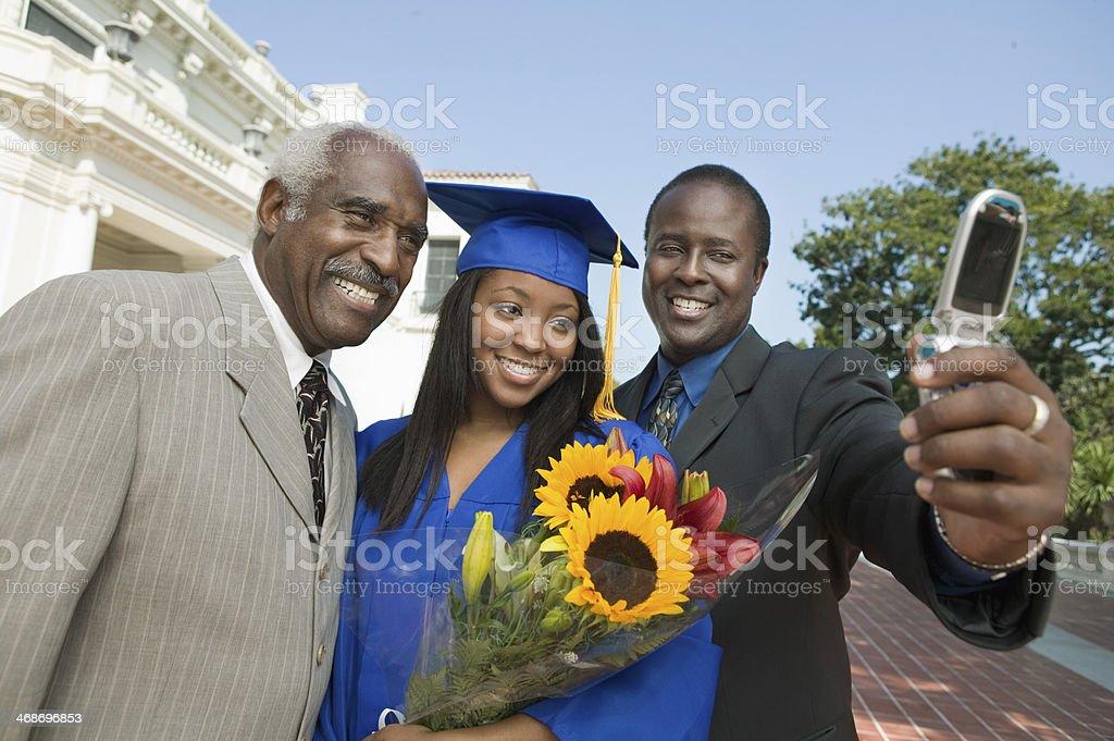 Graduados tomando fotos con padre y abuelo - foto de stock