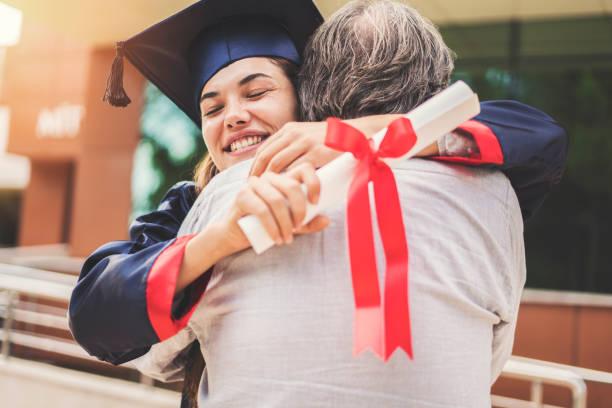 étudiant diplômé étreindre son père - remise de diplôme photos et images de collection