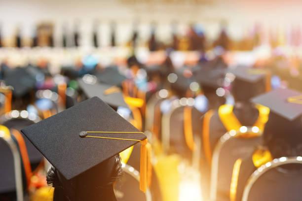graduates in graduation ceremony - university стоковые фото и изображения