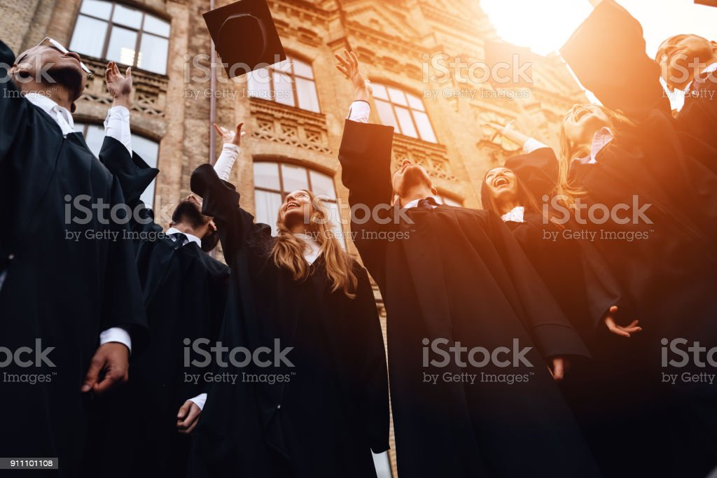 Graduates of the university toss their caps up. stock photo