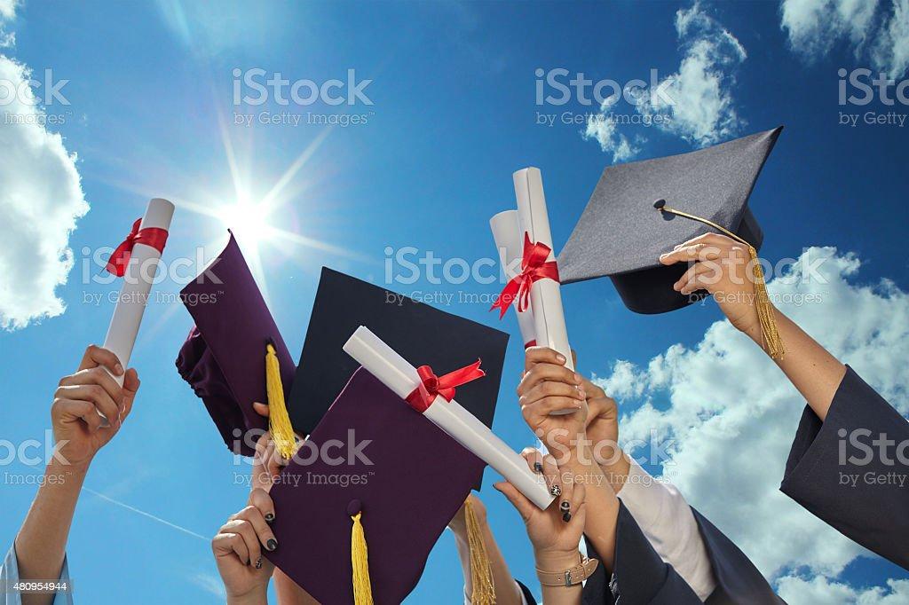 graduates stutents graduates stutents  throwing graduation hats in the air. 2015 Stock Photo
