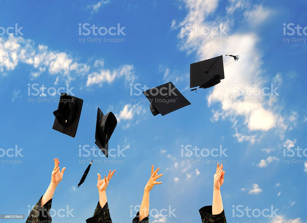 graduates throwing graduation hats in the air. stock photo