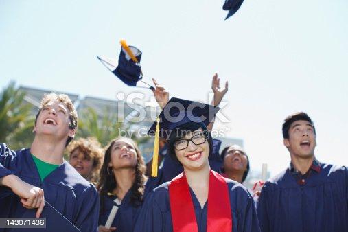 istock Graduates tossing caps in air outdoors 143071436