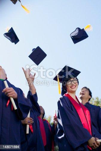 istock Graduates tossing caps in air outdoors 143071594