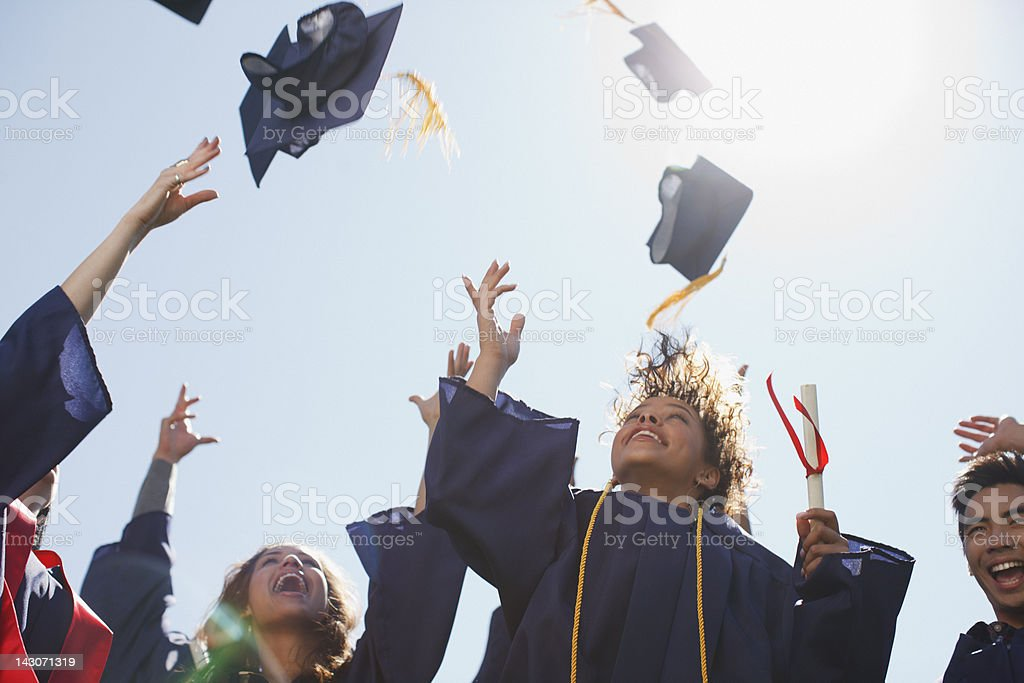 Graduates tossing caps into the air stock photo