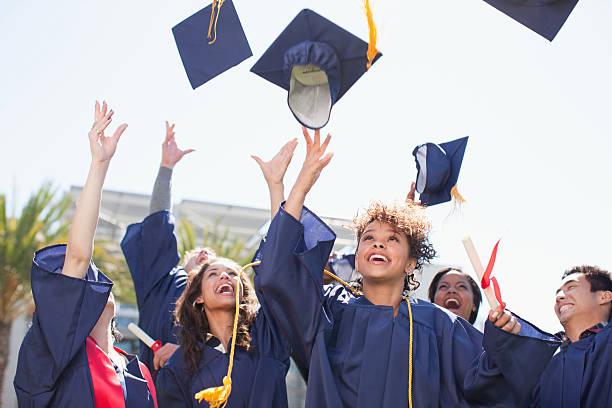 graduados tossing tapas en el aire - graduación fotografías e imágenes de stock