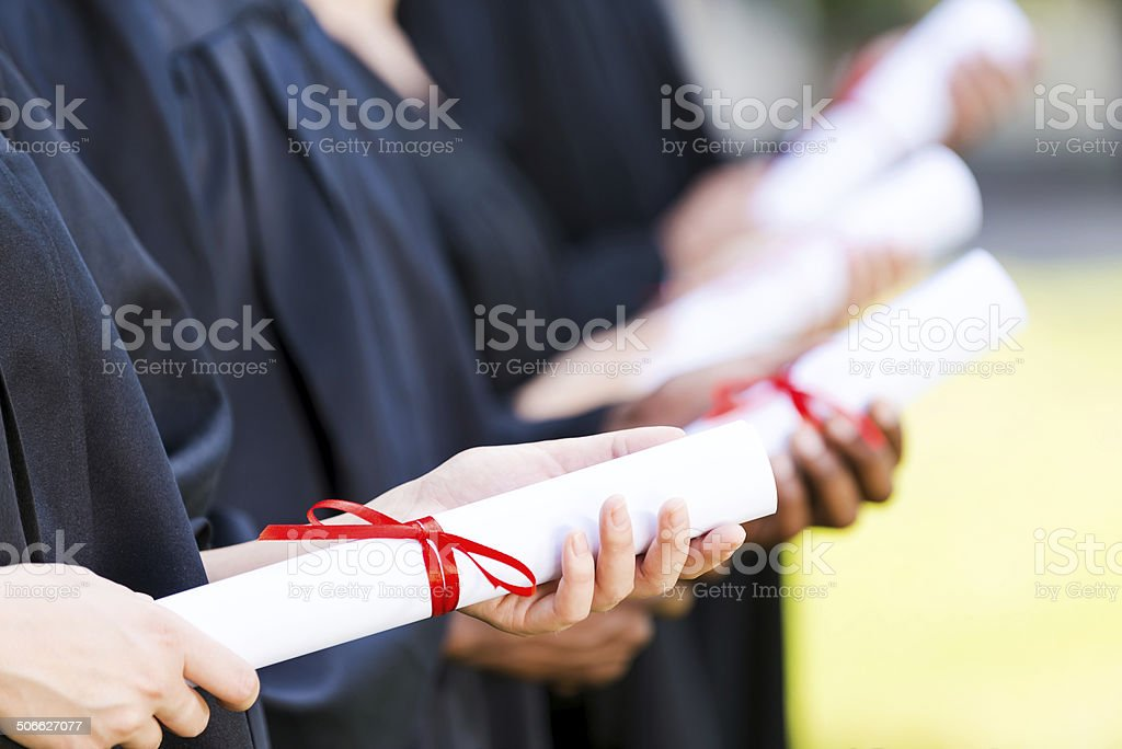 Graduates with diplomas. stock photo