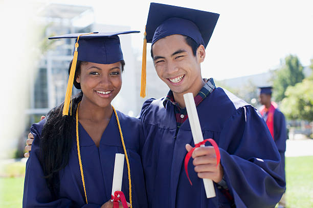 Graduates with diplomas smiling together stock photo