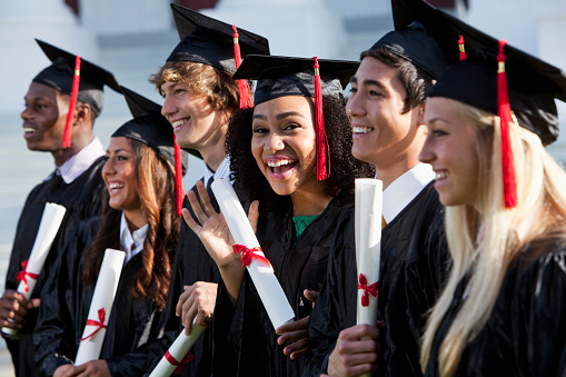 Multi-ethnic friends graduating together, in cap and gown.   Main focus on African American girl in middle, waving at camera.
