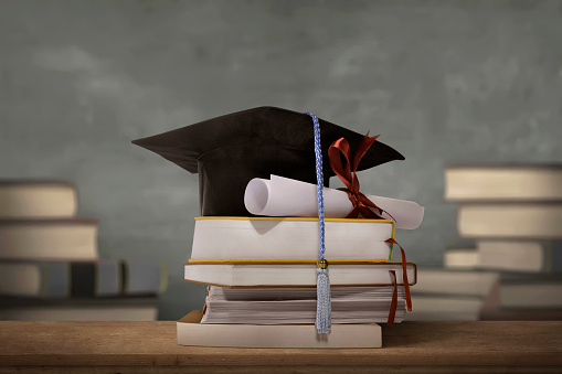 istock Graduation cap above stack books with degree paper 661318146