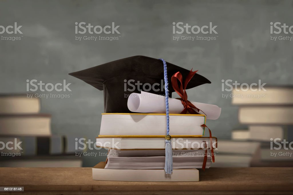 Graduation cap above stack books with degree paper stock photo