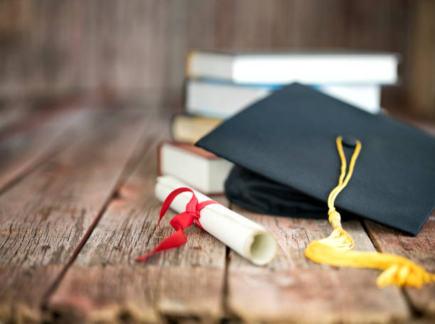 Graduation Cap and Diploma Concept on a Wood Background stock photo