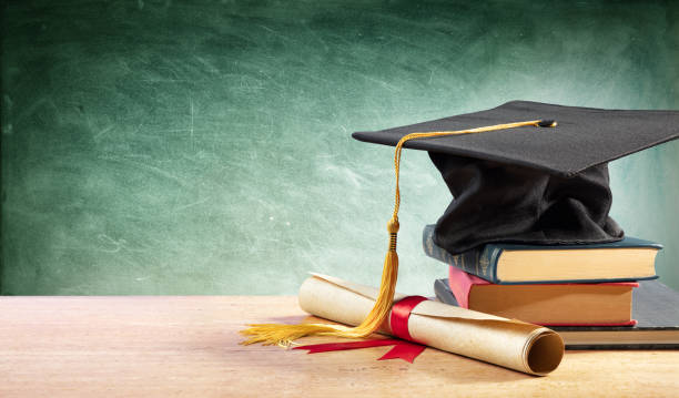 gorra de graduación y diploma en mesa con libros - graduación fotografías e imágenes de stock