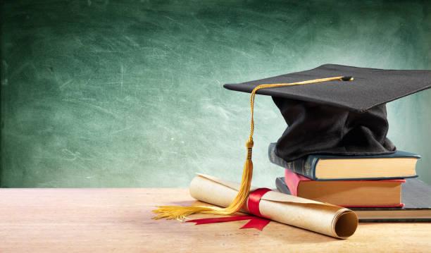 mezuniyet cap ve kitaplar ile masa üzerinde diploma - graduation stok fotoğraflar ve resimler