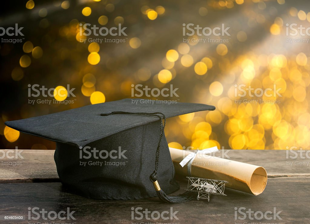 graduation cap, hat with degree paper on wood table, abstract stock photo