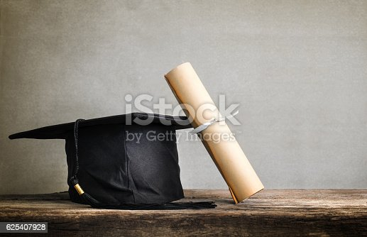 istock graduation cap, hat with degree paper on wood table Empty 625407928