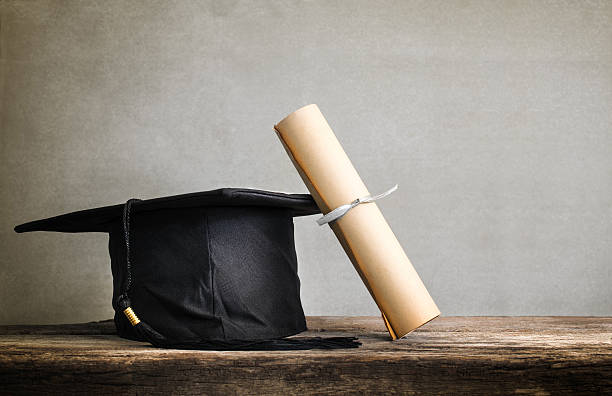 graduation cap, hat with degree paper on wood table Empty stock photo
