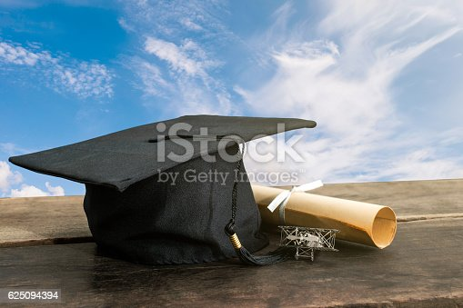 graduation cap, hat with degree paper on wood table, sky background Empty ready for your product display or montage.