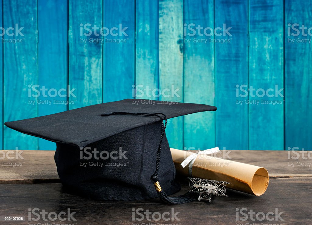 graduation cap, hat with degree paper on wood table, vintage stock photo