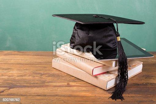 istock Graduation!  Cap, motarboard, digital tablet on books on desk. Education. 520765762