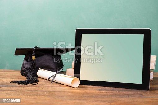 istock Graduation!  Cap, motarboard, diploma, digital tablet on desk.  Education. 520556658