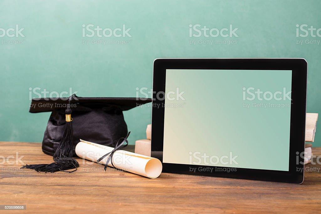 Graduation!  Cap, motarboard, diploma, digital tablet on desk.  Education. stock photo