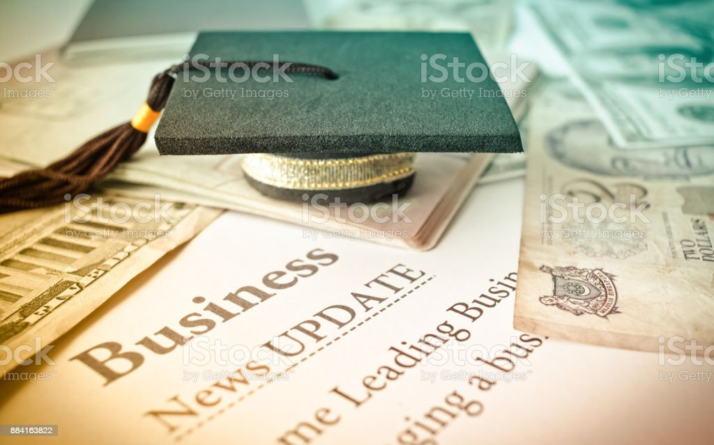 Graduation cap on a letter book, Business News update, Concept of graduate education MBA abroad in university, requires a lot foreign currency Dollars to bring success in famous institution. stock photo